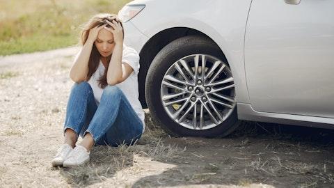 Kvinne som tar seg til hode på bakken utenfor bilen sin.