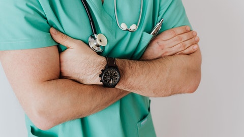 En lege i grønn drakt står med armene i kryss.