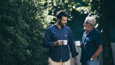 To menn snakker sammen mens de går tur.