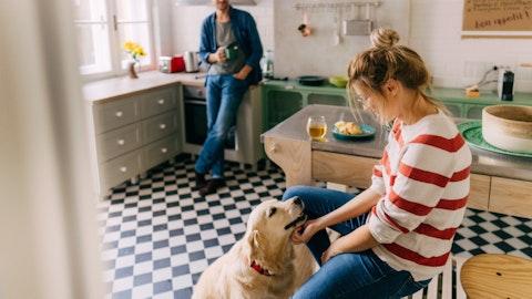 Et kjærestepar og en hund på kjøkkenet.