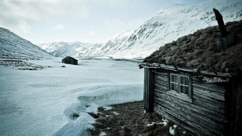 Gårdsbruk på fjellet dekket av snø.