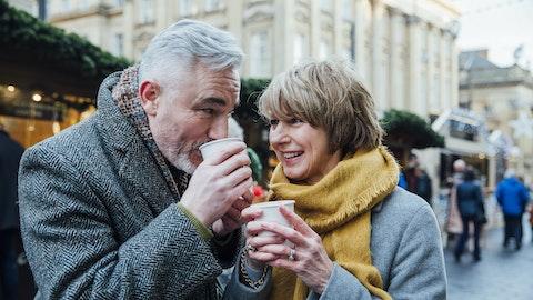 En mann og en kvinne drikker varm sjokolade på julemarkedet.