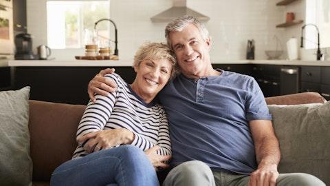 Et eldre par sitter i sofaen og smiler.