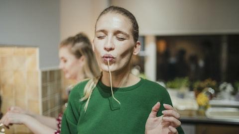 En kvinne som spiser spaghetti på kjøkkenet.