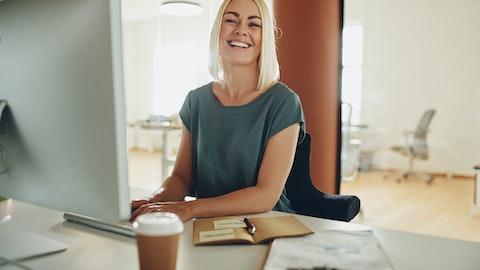 Smilende blond kvinne foran en PS-skjerm