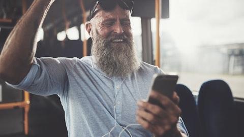 En mann som ser på sin telefon og smiler på en buss.