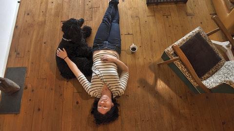 En kvinne ligger på gulvet sammen med hunden sin.