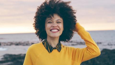 En glad dame som smiler inn i kameraet.