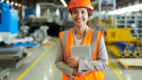 Kvinnelig anleggsarbeider med iPad i hendene.