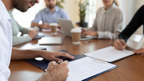 En gruppe mennesker som signerer avtaler.