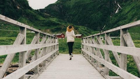 En jente i ullgenser som jobber over en bro i et hyttelandskap.