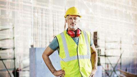 Anleggsarbeider i gul refleksvest på byggeplass.