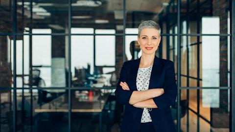 Forretningskvinne ser inn i kameraet i et moderne lokale.