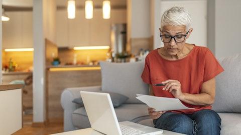 Kvinne som leser noen dokumenter i stuen sin.