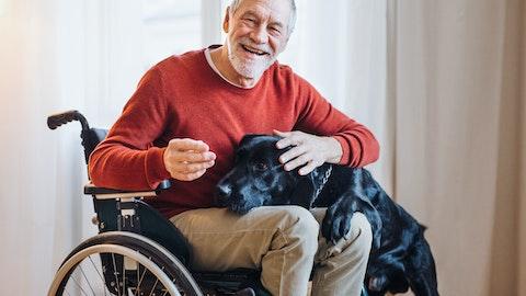 Glad mann i rullestol med en hund på fanget.