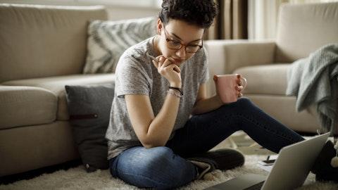 En kvinne som sitter på gulvet og arbeider.