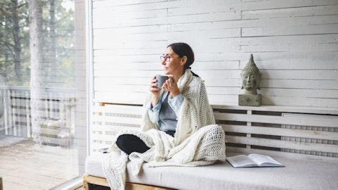 Kvinne som sitter i et lyst rom med pledd og kakao.